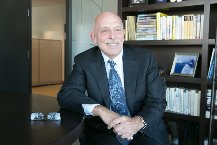 CEO & Chairman, John Nicola sitting at his desk discussing achieving excellence